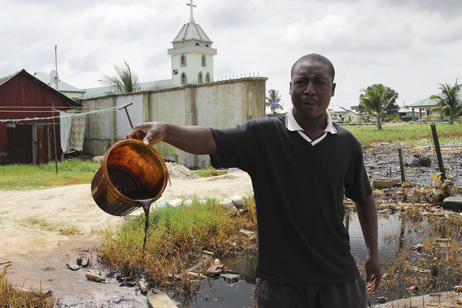 A villager shows a bucket of of crude oil spill at the banks of a river, after a Shell pipeline leaked, in the Oloma community in Nigeria's delta region (Reuters/Tife Owolabi)